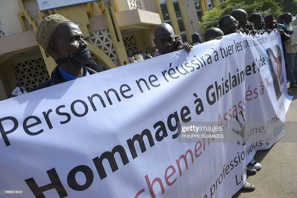 Malian journalists hold a banner during a white march on November 4, 2013 in Bamako, in memory of Radio France Internationale (RFI) journalist Ghislaine Dupont and sound technician Claude Verlon killed in the town of Kidal. French troops were working today with Malian security forces to hunt the killers of the two French journalists shot dead in the west African nation's rebel-infested northern desert. Ghislaine Dupont, 57, and Claude Verlon, 55, were kidnapped and killed by what French Foreign Minister Laurent Fabius said were 'terrorist groups' in the flashpoint northeastern town of Kidal on November 2, 2013. AFP PHOTO / PHILIPPE DESMAZES