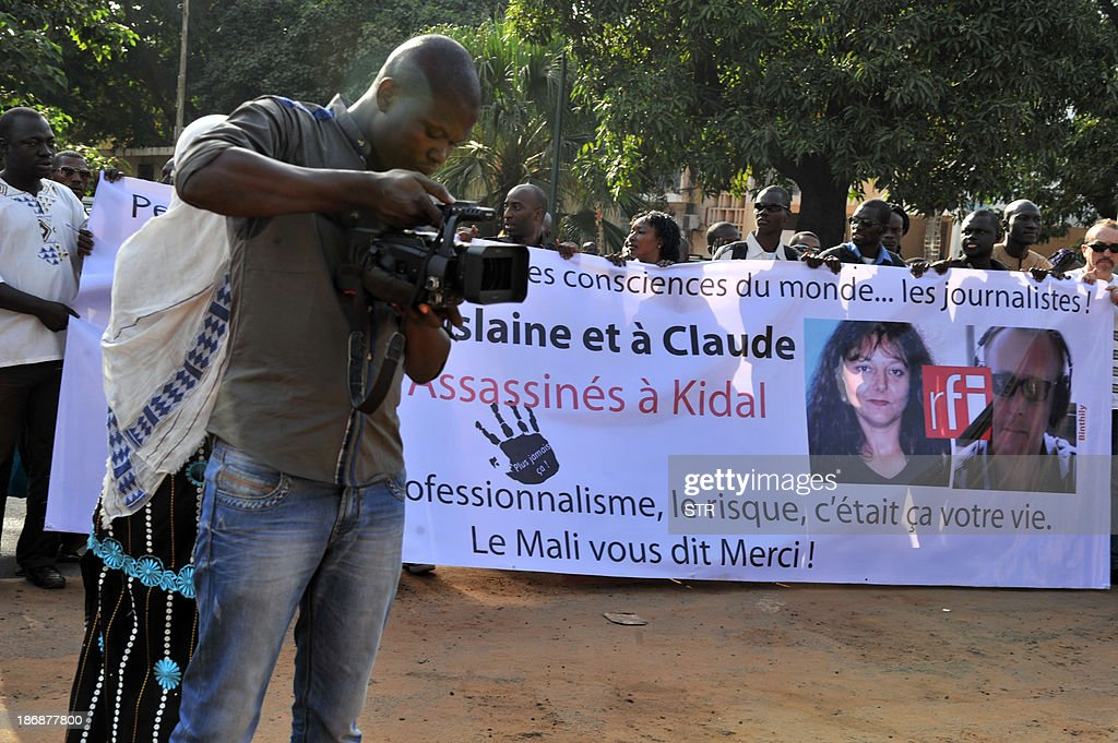 Malian journalists hold a banner showing portraits of Radio France Internationale (RFI) journalist Ghislaine Dupont and sound technician Claude Verlon killed in the town of Kidal, during a white march in their memory on November 4, 2013 in Bamako. French troops were working today with Malian security forces to hunt the killers of the two French journalists shot dead in the west African nation's rebel-infested northern desert. Ghislaine Dupont, 57, and Claude Verlon, 55, were kidnapped and killed by what French Foreign Minister Laurent Fabius said were 'terrorist groups' in the flashpoint northeastern town of Kidal on November 2, 2013.