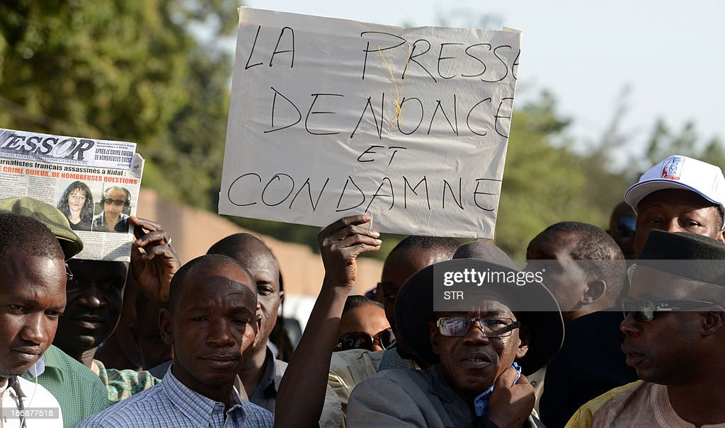 Malian journalists hold a placard in French reading 'Press denounces and condemns' during a white march on November 4, 2013 in Bamako, in memory of Radio France Internationale (RFI) journalist Ghislaine Dupont and sound technician Claude Verlon killed in the town of Kidal. French troops were working today with Malian security forces to hunt the killers of the two French journalists shot dead in the west African nation's rebel-infested northern desert. Ghislaine Dupont, 57, and Claude Verlon, 55, were kidnapped and killed by what French Foreign Minister Laurent Fabius said were 'terrorist groups' in the flashpoint northeastern town of Kidal on November 2, 2013.