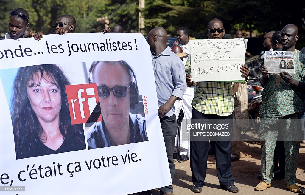 Malian journalists hold banners during a white march on November 4, 2013 in Bamako, in memory of Radio France Internationale (RFI) journalist Ghislaine Dupont (L) and sound technician Claude Verlon (R) killed in the town of Kidal. French troops were working today with Malian security forces to hunt the killers of the two French journalists shot dead in the west African nation's rebel-infested northern desert. Ghislaine Dupont, 57, and Claude Verlon, 55, were kidnapped and killed by what French Foreign Minister Laurent Fabius said were 'terrorist groups' in the flashpoint northeastern town of Kidal on November 2, 2013.