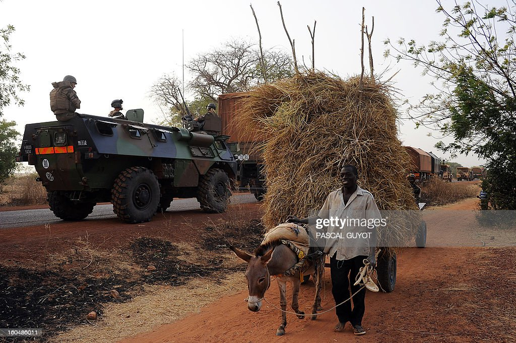 A Malian man guiding a mule-drawn carriage walks past a convoy of French army vehicules and French soldiers arriving in Sevare, in the Mopti region of Mali, on February 1, 2013. President Francois Hollande prepared to visit Mali as French-led troops worked today to secure the last Islamist stronghold in the north after a lightning offensive against the extremists. Hollande, whose surprise decision to intervene in Mali three weeks ago has won broad support at home, will travel to the fabled city of Timbuktu and hold a working lunch in the capital with Mali's interim president Dioncounda Traore, the Malian presidency said.