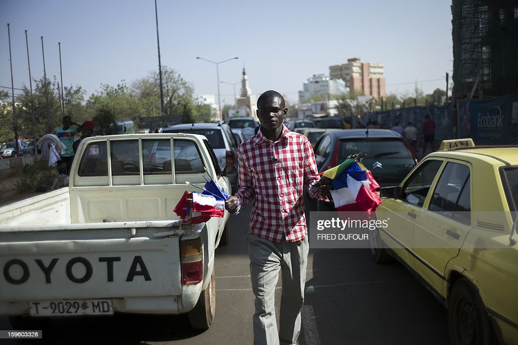A Malian man sells flags, including French ones, on a street of Bamako on January 17, 2013. France now has 1,400 troops on the ground in Mali, more than half the total of 2,500 it plans to deploy in its former colony, Defence Minister Jean-Yves Le Drian said on Thursday.