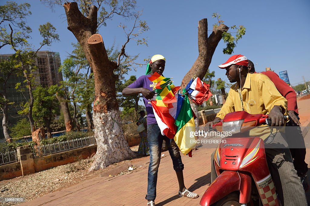 A Malian man sells flags on January 18, 2013 in a street of Bamako. French Foreign Minister Laurent Fabius said he would attend an emergency summit of the west African bloc ECOWAS on Saturday to help accelerate the deployment of an African military force in Mali. AFP PHOTO / ERIC FEFERBERG