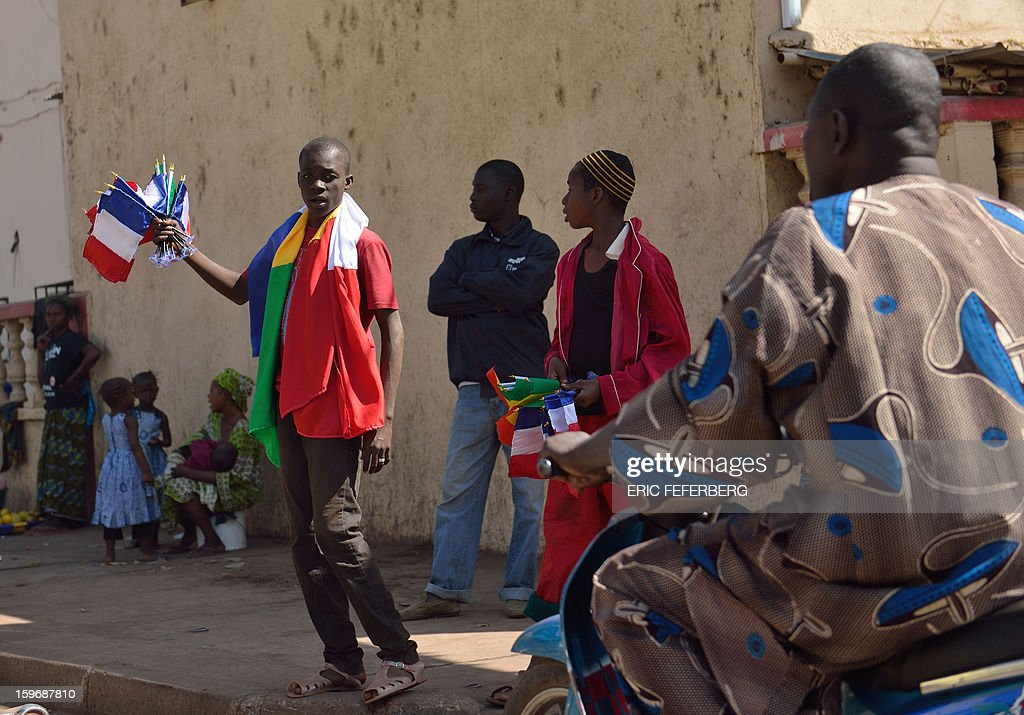 A Malian man sells French flags on January 18, 2013 in a street of Bamako. French Foreign Minister Laurent Fabius said he would attend an emergency summit of the west African bloc ECOWAS on Saturday to help accelerate the deployment of an African military force in Mali.