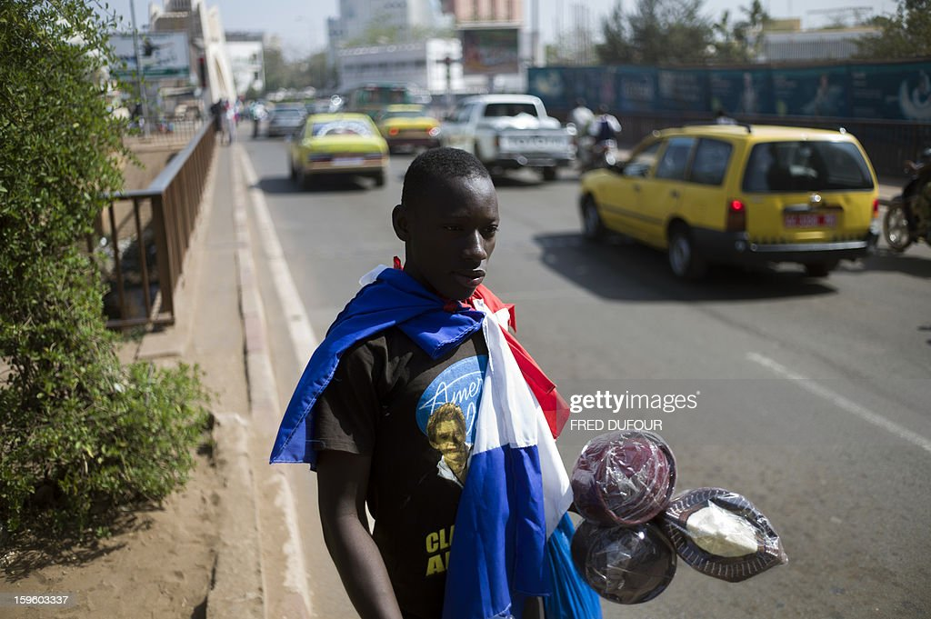 A Malian man sells souvenirs, including French ones, on a street of Bamako on January 17, 2013. France now has 1,400 troops on the ground in Mali, more than half the total of 2,500 it plans to deploy in its former colony, Defence Minister Jean-Yves Le Drian said on Thursday.AFP PHOTO / FRED DUFOUR