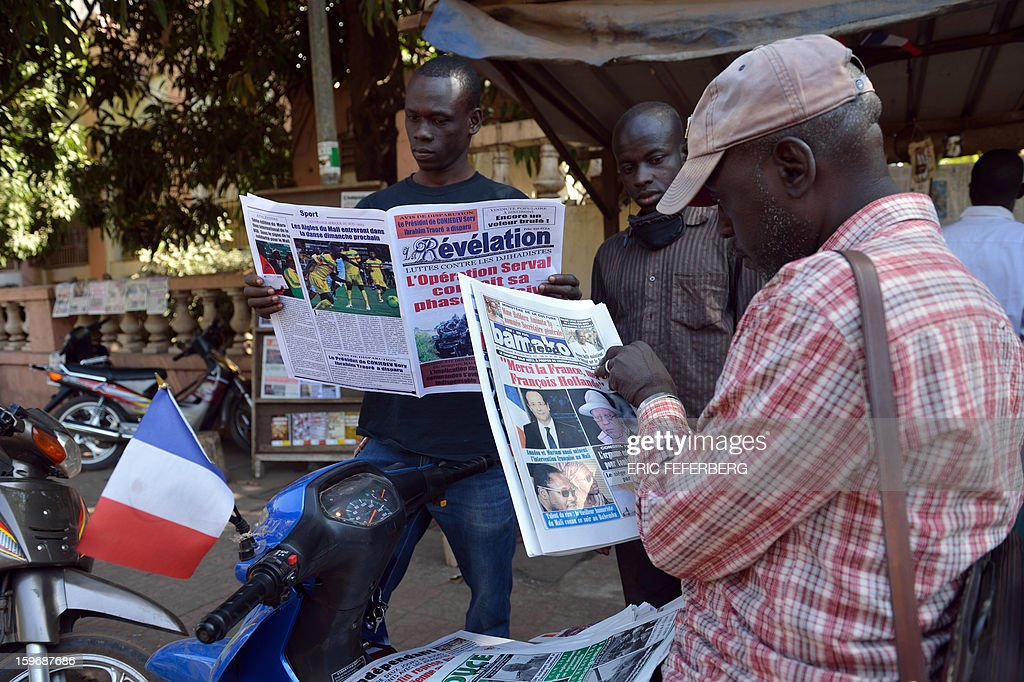 A Malian man sitting on a scooter displaying a French flag reads the newspapers on January 18, 2013 in a street of Bamako. French Foreign Minister Laurent Fabius said he would attend an emergency summit of the west African bloc ECOWAS on Saturday to help accelerate the deployment of an African military force in Mali. AFP PHOTO / ERIC FEFERBERG
