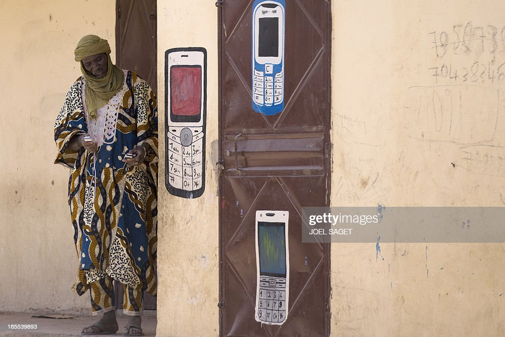 A Malian man uses his mobile phone in front of a phone shop on April 4, 2013 in Gao. The United Nations expressed concern over reprisal attacks against ethnic Tuaregs and Arabs in Mali, where a French-led intervention recently routed Islamist rebels. AFP PHOTO / JOEL SAGET
