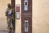 A Malian man uses his mobile phone in front of a phone shop on April 4 2013 in Gao The United Nations expressed concern over reprisal attacks against...