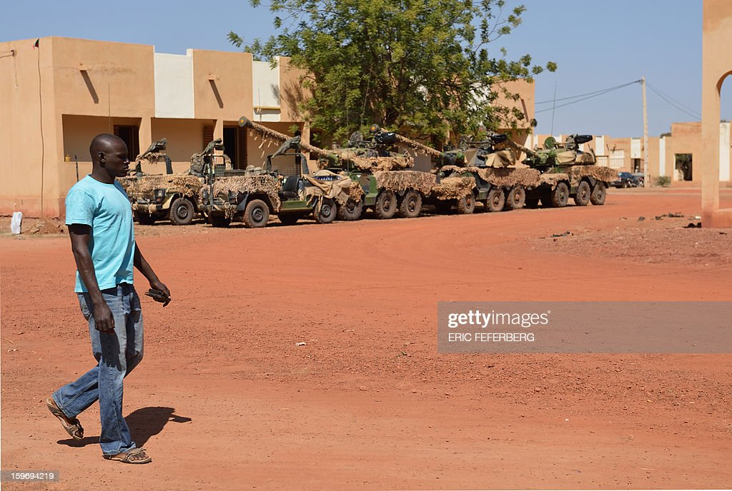 A Malian man walks by Sagaie tanks used by French soldiers from the 21st Rima, near the Malian army 101 airbase, where French troops are stationed, on January 18, 2013, near Bamako. France now has 1,800 troops on the ground in Mali, inching closer to the goal of 2,500 it plans to deploy in its African former colony, Defence Minister Jean-Yves Le Drian said today. That was 400 more than a day earlier, said the minister as he met with French special forces in the western port of Lorient. The troops have been sent to help the Malian army regain control of the north from Islamist groups.