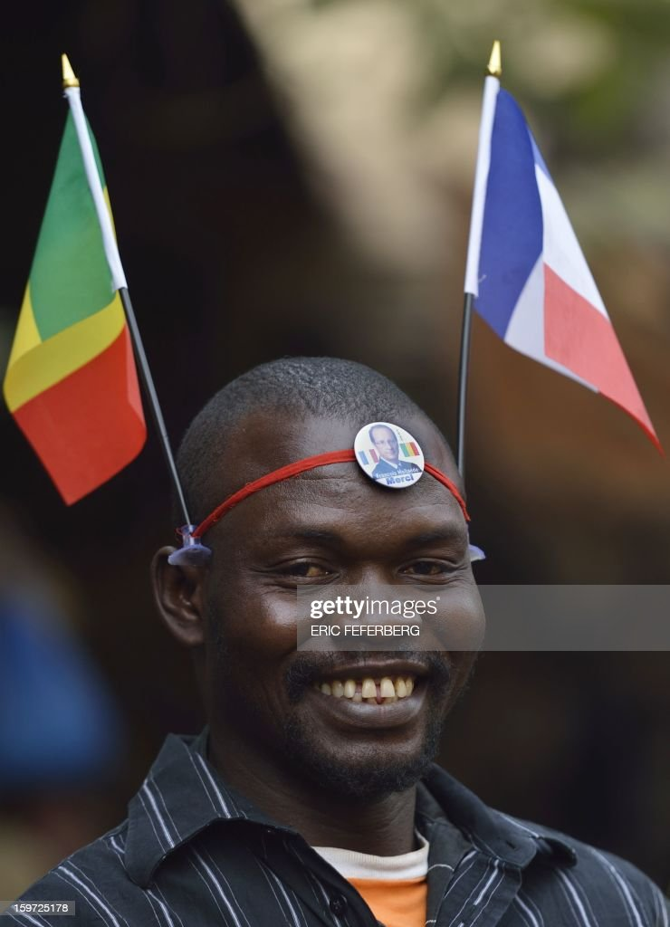 A Malian man wears a French and a Malian flag on his head and a lapel pin reading 'Francois Hollande, Thank You' at a market in Bamako, on January 19, 2013. Meanwhile West African leaders sought urgent UN aid for a regional force to fight Islamists in Mali as President Francois Hollande said French troops would remain as long as needed to stamp out 'terrorism'. AFP PHOTO / ERIC FEFERBERG