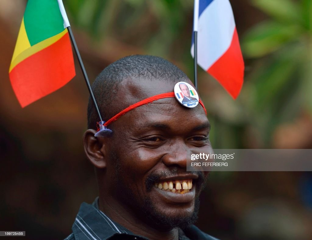 A Malian man wears a French and a Malian flag on his head and a lapel pin reading 'Francois Hollande, Thank You' at a market in Bamako, on January 19, 2013. Meanwhile West African leaders sought urgent UN aid for a regional force to fight Islamists in Mali as President Francois Hollande said French troops would remain as long as needed to stamp out 'terrorism'.