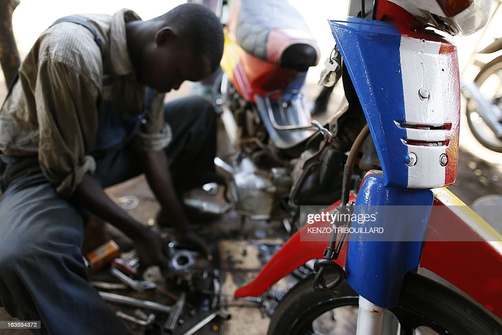 A Malian man works on a scooter painted in the Malian and French colours in Bamako on March 12, 2013. French and Chadian forces are hunting Islamists rebels in northeastern Mali following a French-led intervention that drove the militants from cities in northern Mali they had seized last year.