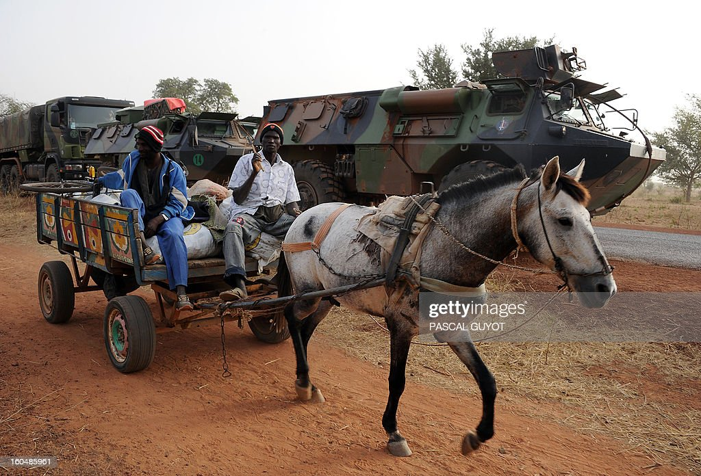 Malian men ride a horse-drawn carriage as they go past a convoy of French army vehicules and French soldiers arriving in Sevare, in the Mopti region of Mali, on February 1, 2013. President Francois Hollande prepared to visit Mali as French-led troops worked today to secure the last Islamist stronghold in the north after a lightning offensive against the extremists. Hollande, whose surprise decision to intervene in Mali three weeks ago has won broad support at home, will travel to the fabled city of Timbuktu and hold a working lunch in the capital with Mali's interim president Dioncounda Traore, the Malian presidency said. AFP PHOTO / PASCAL GUYOT