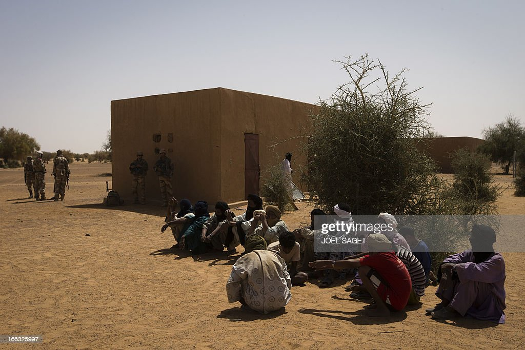 Malian men wait for a meeting with French soldiers on April 9, 2013, 105 kms north of the northeastern Malian city of Gao, during the Operation Gustav, a hunt for Islamist fighters in a valley in northern Mali and one of France's largest military operations during its three-month intervention in its former colony. Operation Gustav comes with France preparing to withdraw three-quarters of the 4,000 troops it deployed in January to block a feared advance on the Malian capital Bamako by Al Qaeda-linked insurgents.