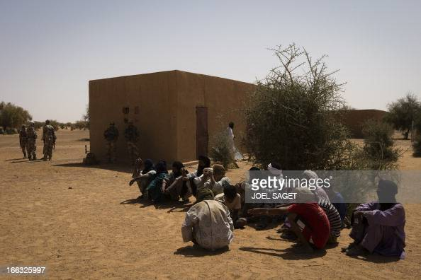 Malian men wait for a meeting with French soldiers on April 9 105 kms north of the northeastern Malian city of Gao during the Operation Gustav a hunt...