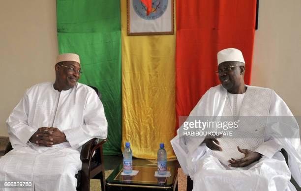 Malian newly appointed Prime Minister Abdoulaye Idrissa Maiga listens to his predecessor Modibo Keita on April 10 2017 during the handover ceremony...