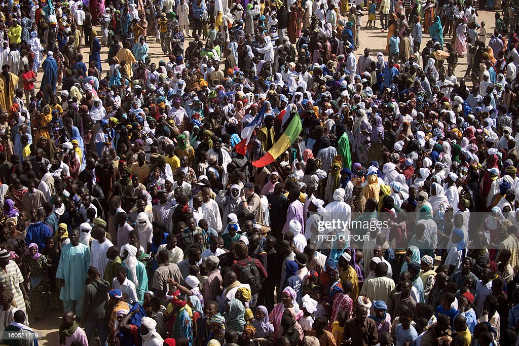 Malian people gather to welcome France's President Francois Hollande as he arrives at Timbuktu, the second step of his one-day visit in Mali, on February 2, 2013. Hollande visits Mali as French-led troops work to secure the last Islamist stronghold in the north after a lightning offensive against the extremists. AFP PHOTO FRED DUFOUR
