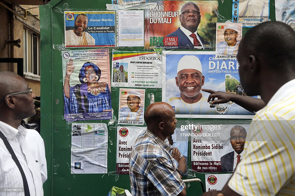 Malian people look at posters displaying candidates for the upcoming presidential election in Mali on July 23, 2013 at the entrance of the Bara centre in Montreuil, a Paris suburb. Mali is hoping against the odds for credible July 28 presidential elections but crucial barriers to an acceptable voter turnout and the ever-present threat of terrorist attacks are casting a long shadow over preparations. The polls are seen as vital to reuniting the country after a March 2012 military coup and a sweeping offensive by Islamist rebels who captured the entire north before being flushed out by French and African troops.
