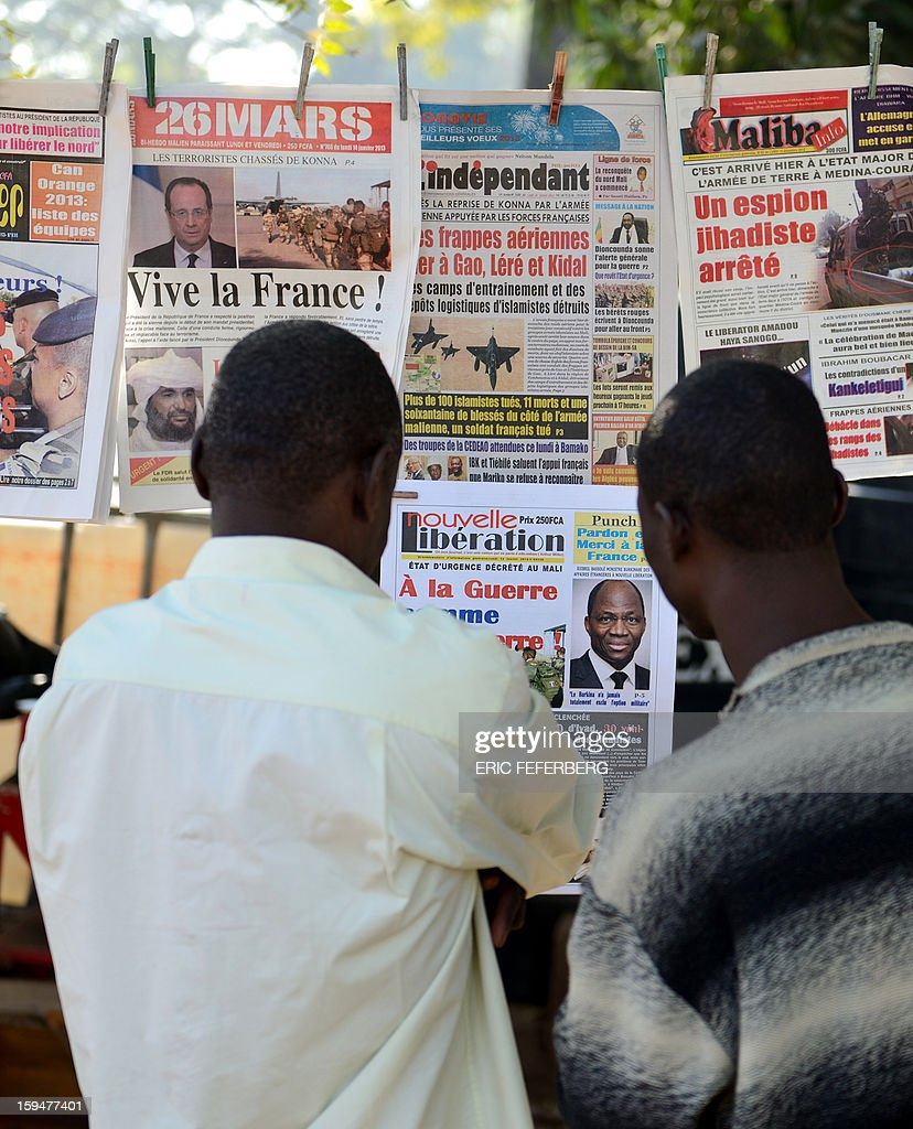 Malian people read newspapers' frontpages bearing headlines on France's military intervention to turn back the terrorist threat in Mali on January 14, 2013 in Bamako. Islamists have retreated in the east of Mali but French forces are facing a difficult situation in the west of the country where rebels are well armed, French Defence Minister said on January 14.