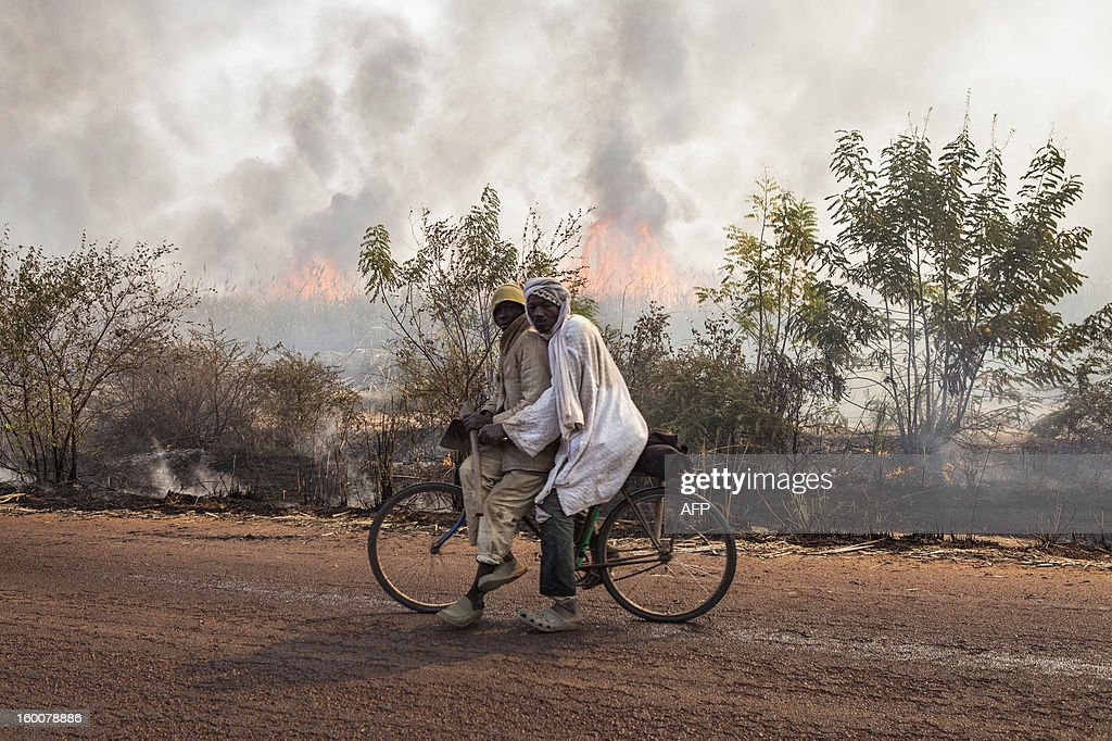 Malian people ride a bike past a sugar cane field on fire before the harvest, on January 23, 2013 on the road to Massina.