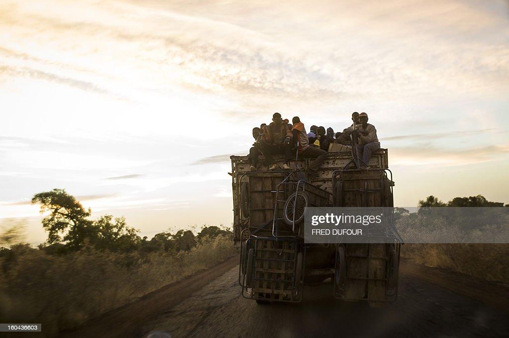 Malian people travel on top of a truck on January 29, 2013 in San, a Malian town near the border with Burkina Faso.
