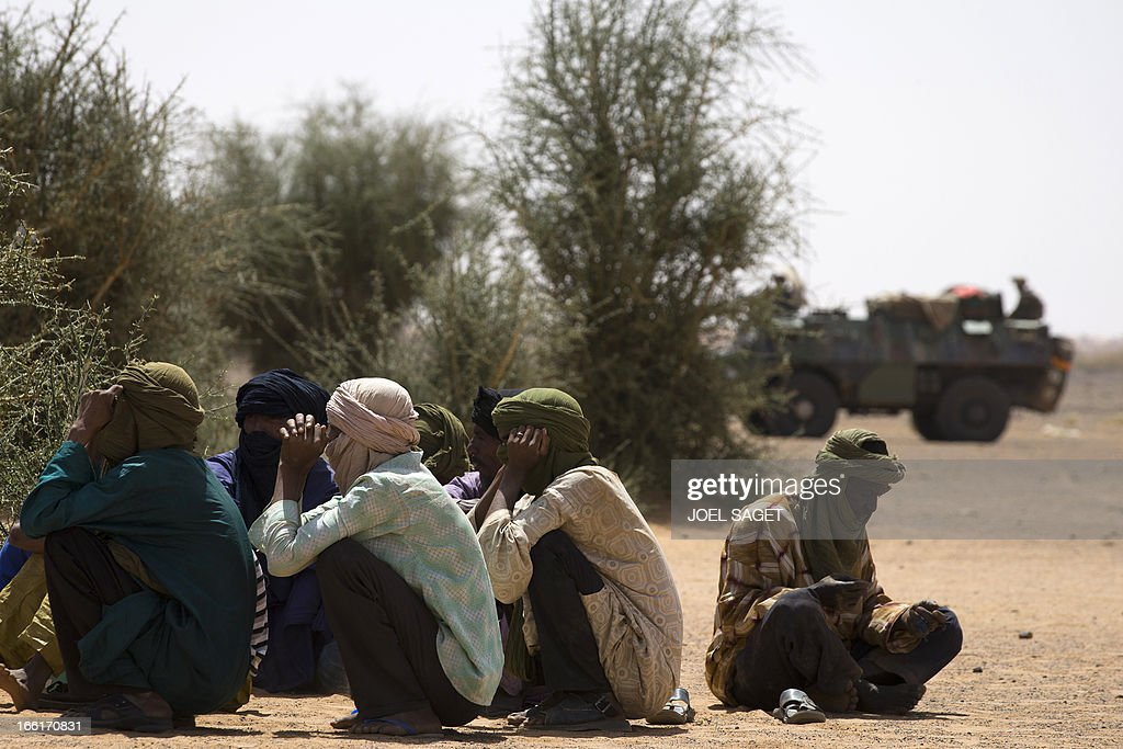 Malian people wait to be questioned by Malian and French soldiers during the Operation Gustav, a hunt for Islamist fighters in a valley in northern Mali and one of France's largest military operations during its three-month intervention in its former colony, on April 9, 2013, 105 km North of Gao. Operation Gustav comes with France preparing to withdraw three-quarters of the 4,000 troops it deployed in January to block a feared advance on the Malian capital Bamako by Al Qaeda-linked insurgents. AFP PHOTO / JOEL SAGET