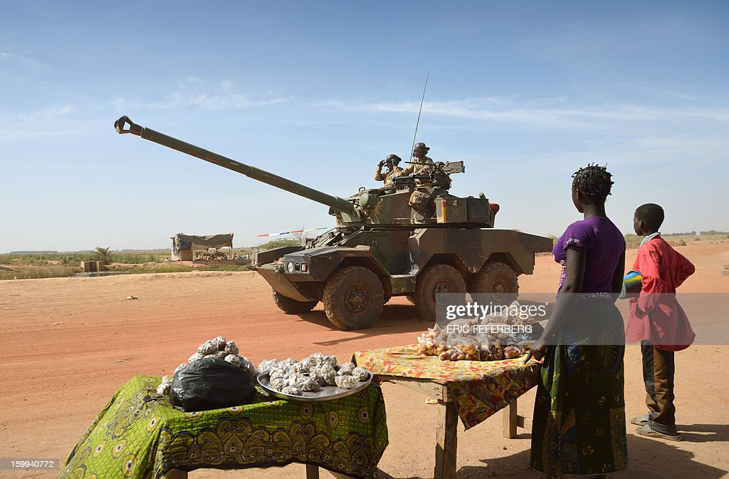 Malian people watch a French Sagaie armoured vehicle patroling on January 23, 2013 in Diabaly, 400 kilometres (250 miles) north of the capital Bamako. French and Malian troops recaptured the frontline towns of Diabaly and Douentza two days ago in a major boost to their push north to flush out Al Qaeda-linked rebels.