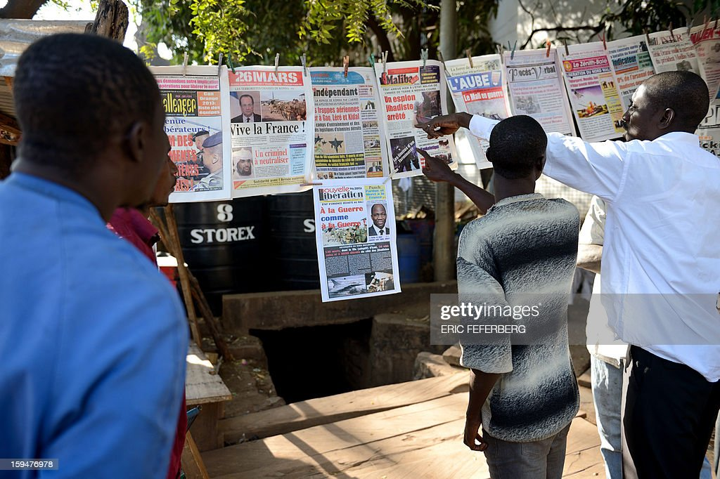 Malian people watch newspapers' frontpages focusing on France's military intervention to turn back the terrorist threat in Mali on January 14, 2013 in Bamako.
