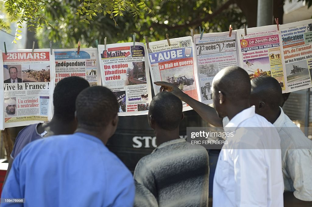 Malian people watch newspapers' frontpages focusing on France's military intervention to turn back the terrorist threat in Mali on January 14, 2013 in Bamako. AFP PHOTO /ERIC FEFERBERG