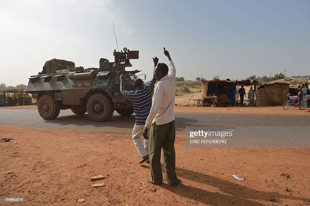 Malian people wave to a French armoured vehicle part of a big convoy coming from Bamako and going to Daibali (400km north of Bamako) on January 24, 2013 in Segou. Paris sent in its forces on January 11 to rescue Mali from Al Qaeda-linked groups controlling the north.