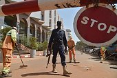 A Malian police officer stands guard as municipal workers clean ouside the Radisson Blu hotel in Bamako on November 22 2015 two days after a deadly...