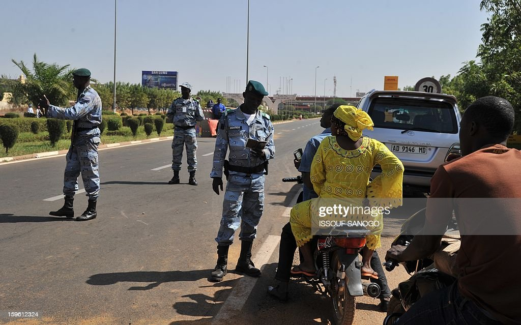 Malian police officers control the identity of a motorcycle's passengers at a checkpoint near Bamako Senou airport on January 17, 2013. France now has 1,400 troops on the ground in Mali, more than half the total of 2,500 it plans to deploy in its former colony, Defence Minister Jean-Yves Le Drian said on Thursday. France won support from European Union nations Thursday for its military campaign in Mali and offers of military aid, possibly including troops, at emergency talks on the crisis. AFP PHOTO / ISSOUF SANOGO