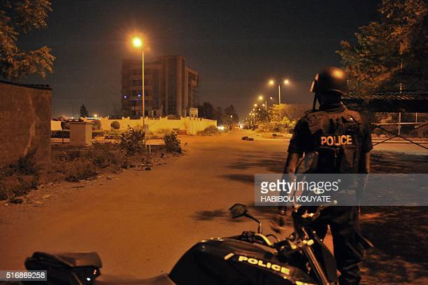 Malian police officers stand guard in a street near a hotel hosting an EU military training mission during an attack in Bamako on March 21 2016 Four...
