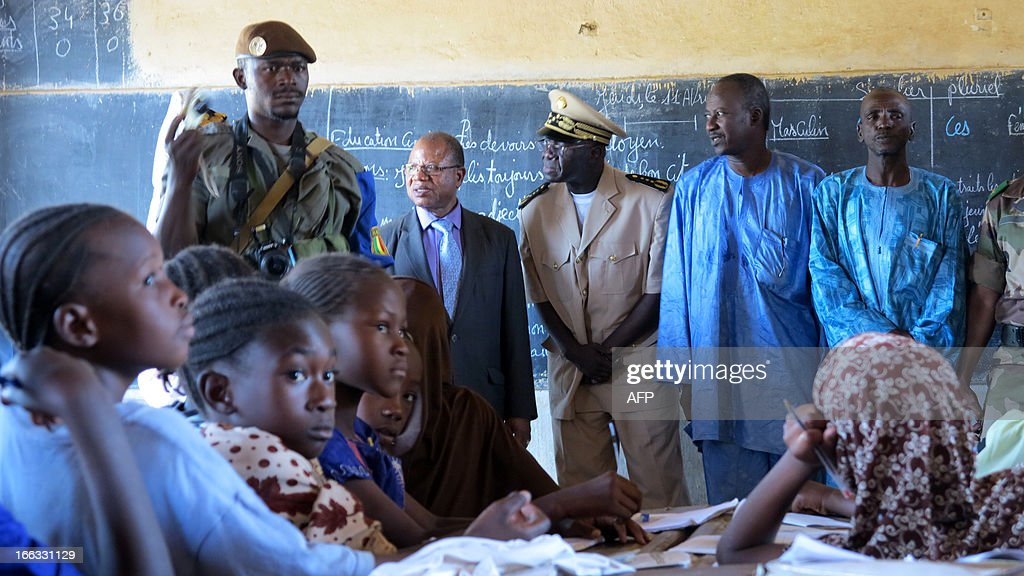 Malian Prime Minister Django Cissoko (2nd L) visits a classroom at Farandjiraye school in Gao on April 11, 2013. Cissoko arrived in the northeastern city of Gao for the first visit there by a head of government since it was overrun by Tuareg rebels more than a year ago. The premier, who was welcomed by local worthies and military personnel, paid tribute to the French troops who intervened to liberate northern Mali from Al Qaeda-linked militias in January. AFP PHOTO / Dorothee Thienot