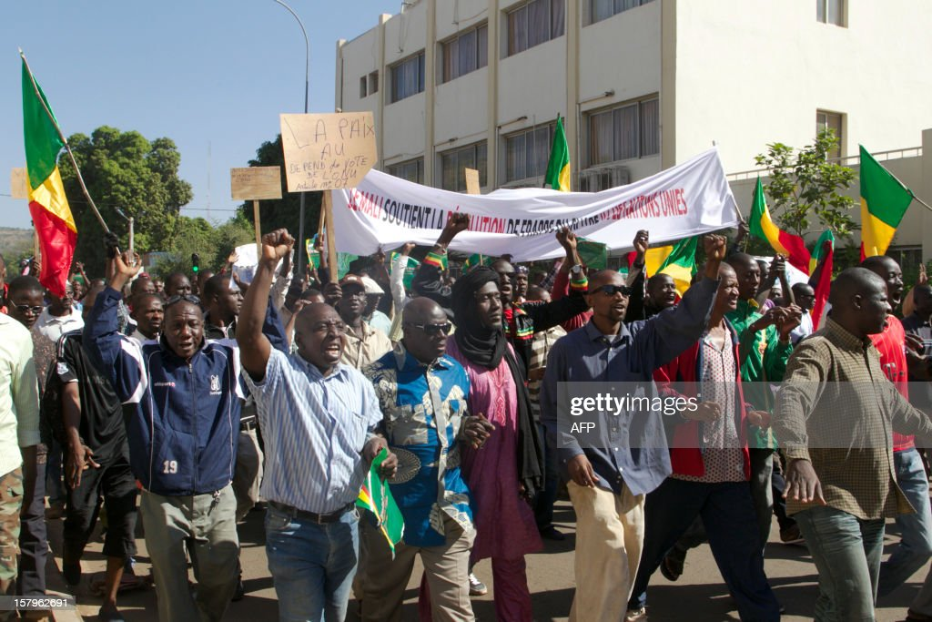 Malian protesters wave their national flag and hold banners in Bamako on December 8, 2012 as they join thousands of others to take part in a demonsration called by several Malian political parties to support the Malian army and demand a United Nations (UN) Security Council resolution approving the deployement of an international force in the country's north, controlled for eight months by Islamist armed groups. Facing the international community's equivocation on the matter, impatience rises in Mali's people, who say they are ready to go to war to take their 'own destiny in hand'. AFP PHOTO / HABIBOU KOUYATE