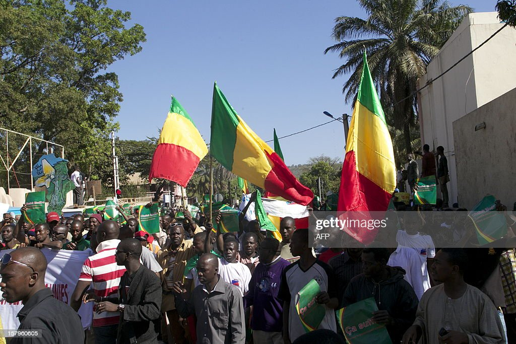 Malian protesters wave their national flag in Bamako on December 8, 2012 as they join thousands of others to take part in a demonsration called by several Malian political parties to support the Malian army and demand a United Nations (UN) Security Council resolution approving the deployement of an international force in the country's north, controlled for eight months by Islamist armed groups. Facing the international community's equivocation on the matter, impatience rises in Mali's people, who say they are ready to go to war to take their 'own destiny in hand'.