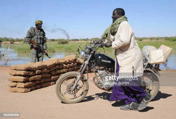 A Malian pushes his motorcycle past a Malian Army checkpoint on February 8 2013 at the site where a suicide bomber blew himself up earlier in the day...