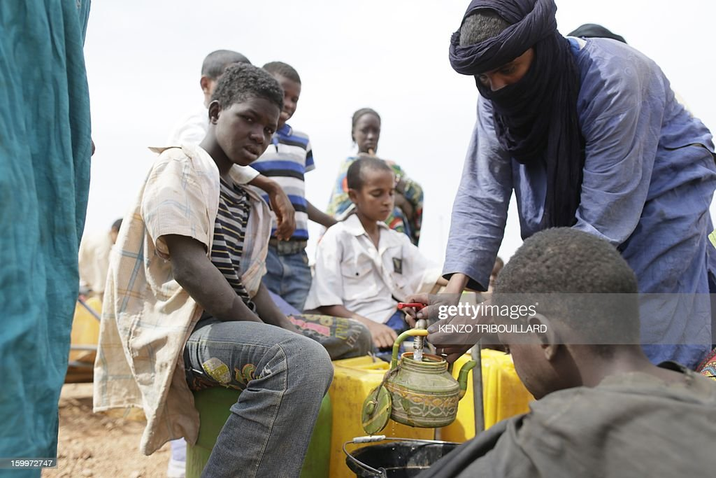 A Malian refugee fills a kettle with water on January 24, 2013 at a refugee camp in Menteao near the Malian border. The conflict in Mali has caused nearly 150,000 people to flee the country, while about another 230,000 are internally displaced, the UN humanitarian agency said on January 15, 2013. According to OCHA, the UN High Commissioner for Refugees has registered 144,500 refugees in neighbouring countries -- 54,100 in Mauritania, 50,000 in Niger, 38,800 in Burkina Faso and 1,500 in Algeria.