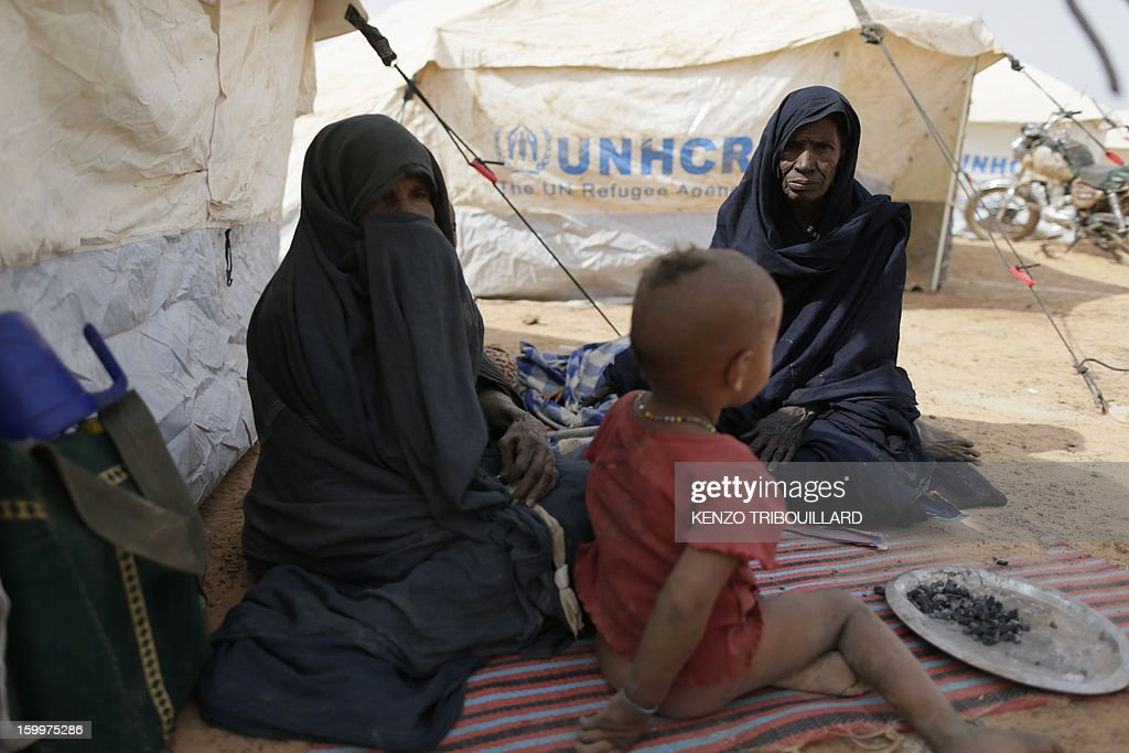 Malian refugee women sit with a child near UNHCR tents, on January 24, 2013 at a refugee camp set in Menteao near the Malian border. The conflict in Mali has caused nearly 150,000 people to flee the country, while about another 230,000 are internally displaced, the UN humanitarian agency said on January 15, 2013. According to OCHA, the UN High Commissioner for Refugees has registered 144,500 refugees in neighbouring countries -- 54,100 in Mauritania, 50,000 in Niger, 38,800 in Burkina Faso and 1,500 in Algeria. AFP PHOTO KENZO TRIBOUILLARD