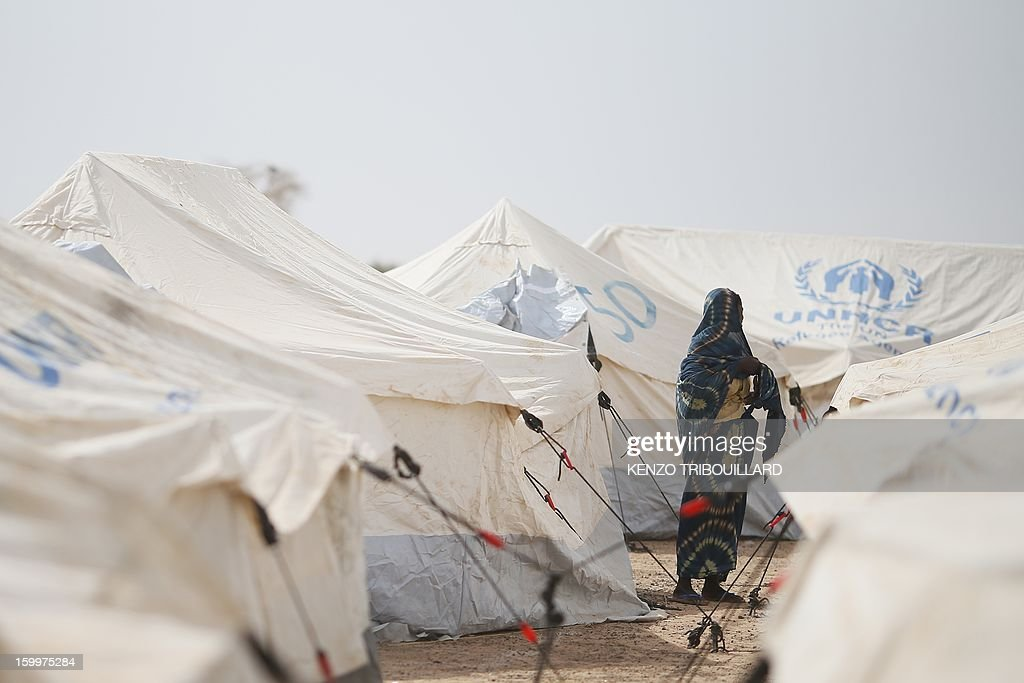 A Malian refugee women stands between UNHCR tents on January 24, 2013 at a refugee camp in Menteao near the Malian border. The conflict in Mali has caused nearly 150,000 people to flee the country, while about another 230,000 are internally displaced, the UN humanitarian agency said on January 15, 2013. According to OCHA, the UN High Commissioner for Refugees has registered 144,500 refugees in neighbouring countries -- 54,100 in Mauritania, 50,000 in Niger, 38,800 in Burkina Faso and 1,500 in Algeria.