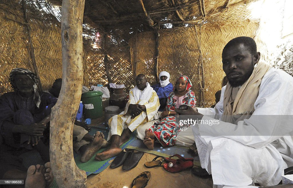 Malian refugees from the Gao region sit in a makeshift home in Ayorou, some 20 km from the border with Mali, on January 27, 2013. The head of the Red Cross has voiced his deep concern about the humanitarian situation in Mali, where French-led forces have been waging an offensive against Islamist groups in the north for over two weeks. KAMBOU