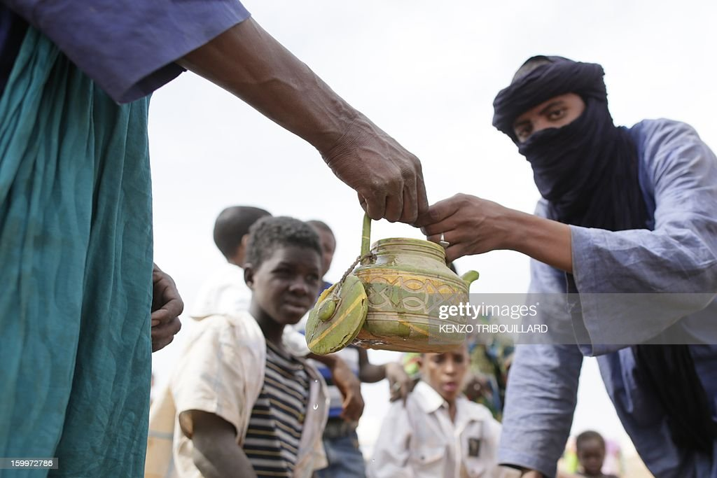 Malian refugees hold a kettle before filling it with water on January 24, 2013 at a refugee camp set in Menteao near the Malian border. The conflict in Mali has caused nearly 150,000 people to flee the country, while about another 230,000 are internally displaced, the UN humanitarian agency said on January 15, 2013. According to OCHA, the UN High Commissioner for Refugees has registered 144,500 refugees in neighbouring countries -- 54,100 in Mauritania, 50,000 in Niger, 38,800 in Burkina Faso and 1,500 in Algeria.