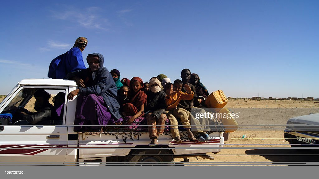 Malian refugees ride in the back of a truck transporting them on a dirt road from Timbuktu to the Mauritanian town of Fassala on January 18, 2013. Since the fighting and airstrikes began, 2,744 Malian refugees had fled the country, with 1,411 entering Mauritania, 848 going to Burkina Faso and 485 arriving in Niger. AFP PHOTO / AL-AKHBAR NEWS AGENCY