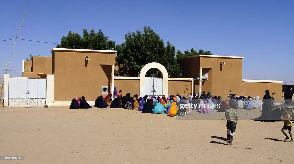 Malian refugees sit in front of the administrive headquarters of the border town of Fassala in Mauritania on January 18, 2013. Since the fighting and airstrikes began, 2,744 Malian refugees had fled the country, with 1,411 entering Mauritania, 848 going to Burkina Faso and 485 arriving in Niger.