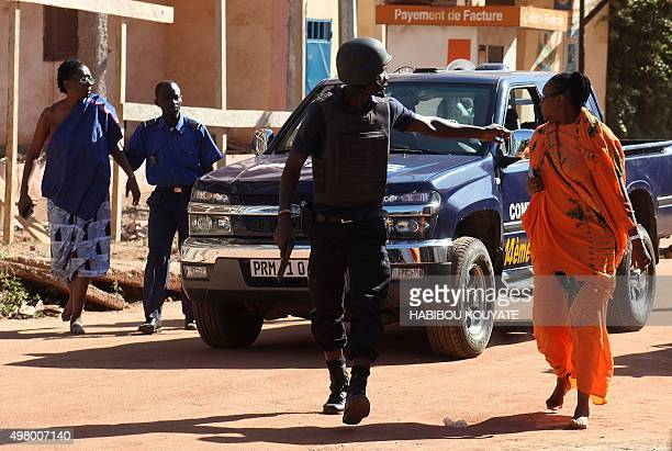 Malian security forces evacuate two women from an area surrounding the Radisson Blu hotel in Bamako on November 20 2015 Gunmen went on a shooting...