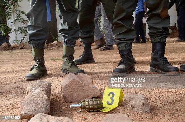 Malian security forces stand guard over a grenade left behind at the site of a blast at La Terrasse bar restaurant in Bamako on March 7 2015 Five...