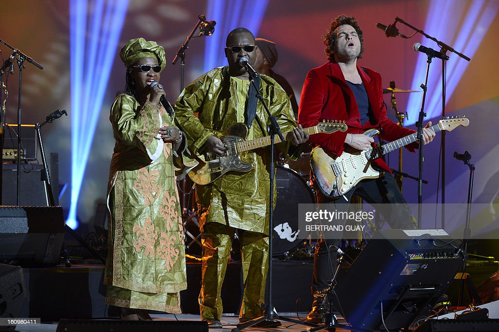 Malian singers Amadou Bagayoko (C) and Mariam Doumbia (L), known as Amadou and Mariam duo perform with French singer Mathieu Chedid, known as M (R) the song 'Africa mon amour' after receiving the best world music album of the year award for their album 'Folila' during the 28th Victoires de la Musique, the annual French music awards ceremony, on February 8, 2013 at the Zenith concert hall in Paris. AFP PHOTO / BERTRAND GUAY