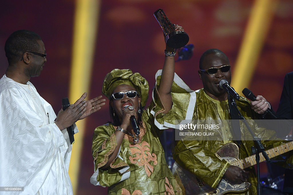 Malian singers Amadou Bagayoko (R) and Mariam Doumbia (C), known as Amadou and Mariam duo, hold their trophy after receiving the best world music album of the year award for their album 'Folila', from Senegalese singer and Minister of Tourism Youssou N'Dour (L) during the 28th Victoires de la Musique, the annual French music awards ceremony, on February 8, 2013 at the Zenith concert hall in Paris.