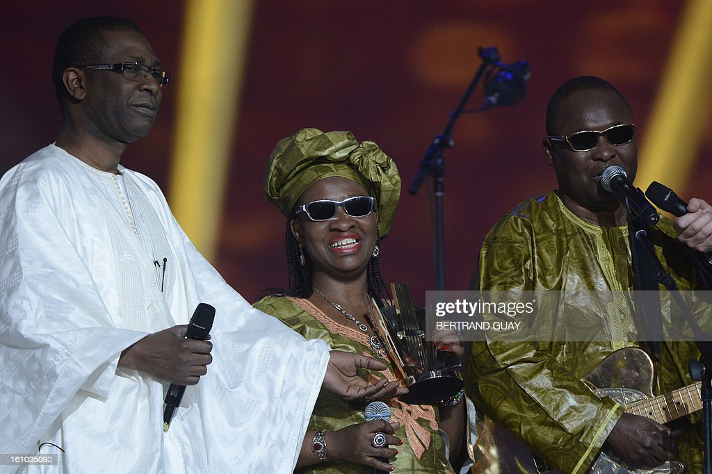 Malian singers Amadou Bagayoko (R) and Mariam Doumbia (C), known as Amadou and Mariam duo, react after receiving the best world music album of the year award for their album 'Folila', from Senegalese singer and Minister of Tourism Youssou N'Dour (L) during the 28th Victoires de la Musique, the annual French music awards ceremony, on February 8, 2013 at the Zenith concert hall in Paris.