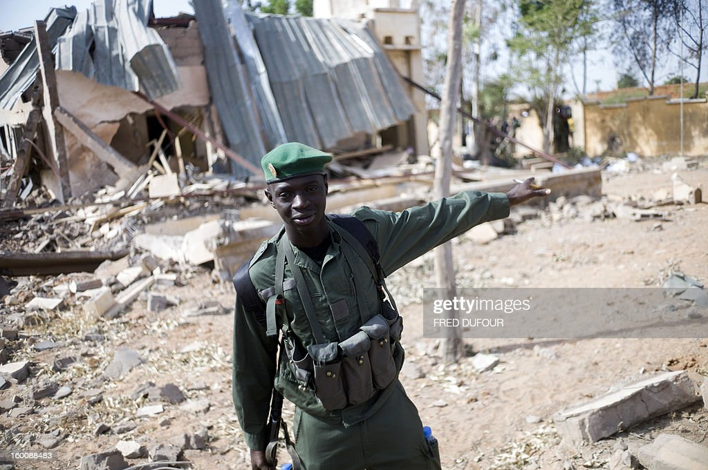 A Malian soldier asks journalists to leave a destroyed area on January 26, 2013 in the key central town of Konna controled by French and Malian army since last week after being taken last January 11 by Islamist groups. French and Malian troops pushed north towards the key Islamist strongholds in northern Mali today, as west African defence chiefs gathered in Ivory Coast to review plans to deploy a regional intervention force. AFP PHOTO / FRED DUFOUR